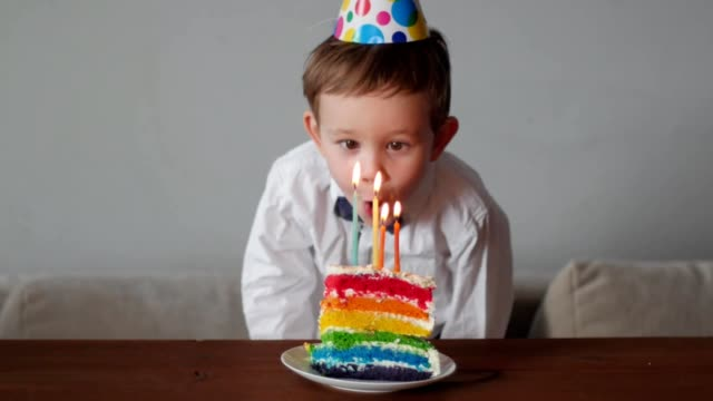 cute boy blowing candles on the rainbow birthday cake video