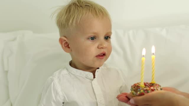 Ein netter Junge bläst zwei Kerzen auf der Torte. – Video