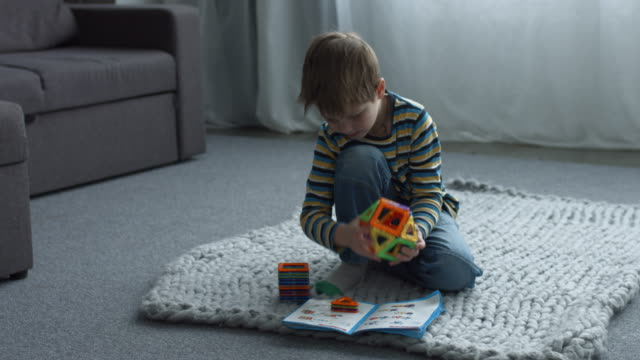 Cute boy constructing from magnetic designer pieces Concentrated adorable preschool boy constructing figure from colorful magnetic designer pieces while sitting on the floor in domestic room. Smart child playing with magnetic constructor toy at home. only boys stock videos & royalty-free footage