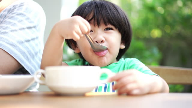 Cute boy eating breakfast with Mother video