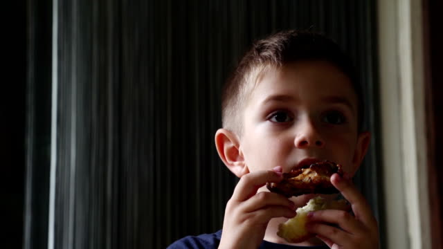 Cute boy eating chicken wing video