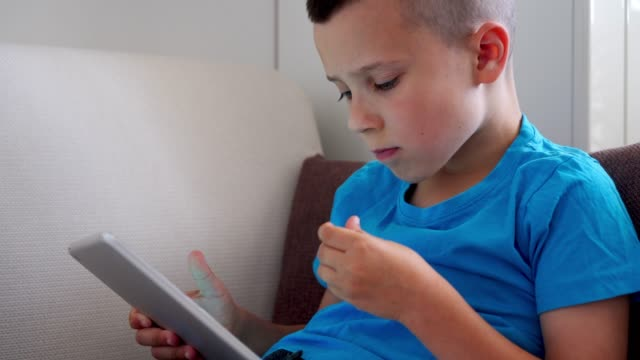 Cute boy eating corn flakes while playing on tablet