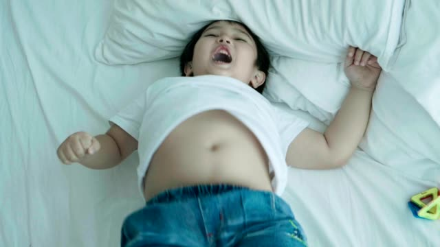Cute boy enjoy jumping and on the bed for happiness moment on weekend video