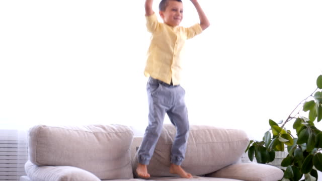 Cute boy having fun while jumping on sofa video