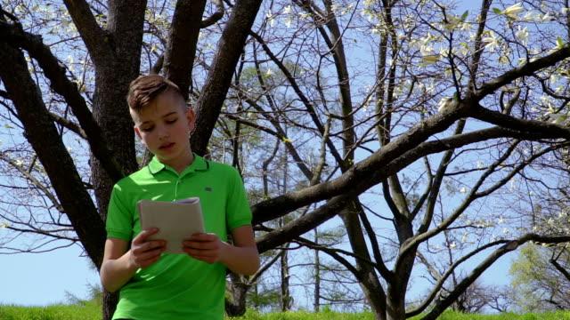 sevimli çocuk defter tutan ağaç parkta üzerinde eğilir - çalışma kitabı stok videoları ve detay görüntü çekimi