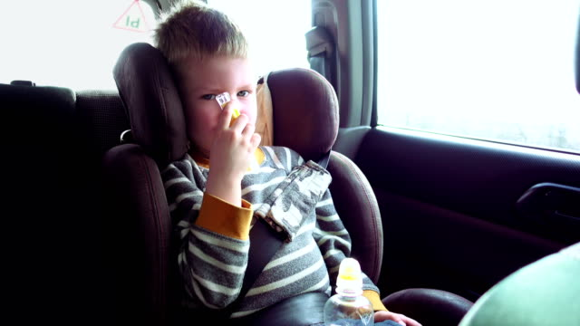Cute boy in a child car seat plays with a toy video