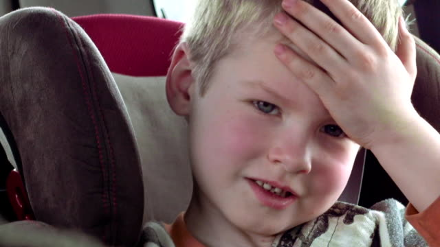 Cute boy in a child car seat smiles and laughs video