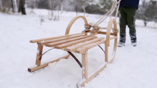 cute boy in warm clothing run pulling wooden sled on snowy winter day. little guy sledding in park on snowfall. tracking shot of child in navy jacket climbing a hill to sledge in forest. slow motion - slitta video stock e b–roll