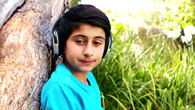 Cute boy listening to music with headphones sitting on the grass