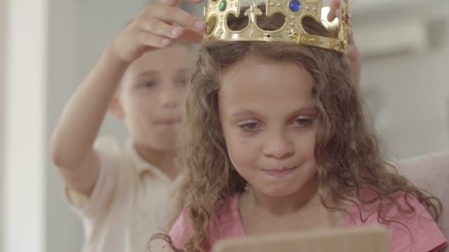 vídeos de stock e filmes b-roll de cute boy putting the crown on the head of adorable curly girl looking in the mirror. - coroa