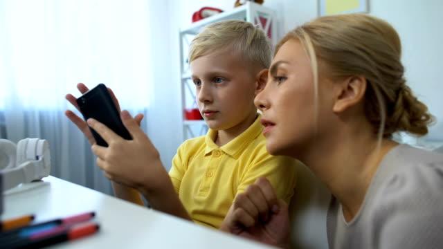 stockvideo's en b-roll-footage met schattige jongen tonen moeder nieuwe smartphone applicatie, moderne technologieën, gadgets - kids online abuse