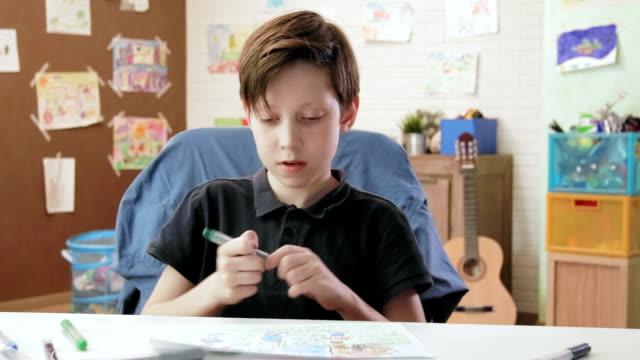 ragazzo carino che mostra la foto della sua famiglia che guarda la telecamera - matita colorata video stock e b–roll