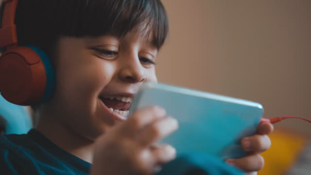 Cute boy sitting on a sofa and watching a cartoon on a mobile phone. Watching cartoons with a happy facial expression. He uses headphones to avoid being disturbed. video