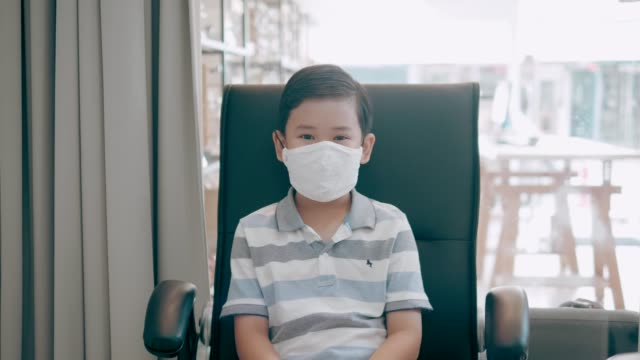 Cute boy smiling behind face mask - Stock Video video