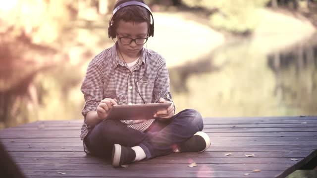 Söt pojke med digital tablett i parken video