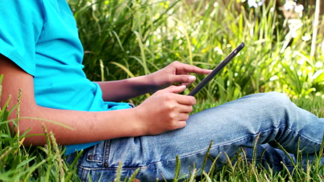 Cute boy using smartphone sitting on the grass