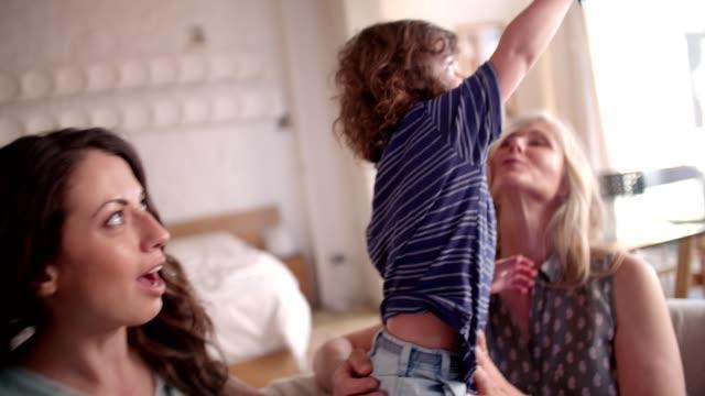 vidéos et rushes de garçon mignon avec sa mère et grand-mère, jouant à la maison - femme seule s'enlacer