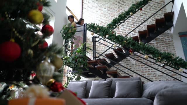 stockvideo's en b-roll-footage met schattige broer en zus wandelen langs de trap op kerst ochtend verrast kijkend naar de kerstboom met geschenken - christmas tree