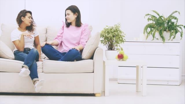 söt kaukasiska och afro-amerikanska flickor sitter i soffan, pratar vänligt och känslomässigt, leende. - kvinna ventilationssystem bildbanksvideor och videomaterial från bakom kulisserna