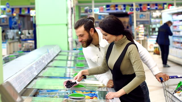 Cute caucasian couple choose frozen foods from the supermarket refrigerator.