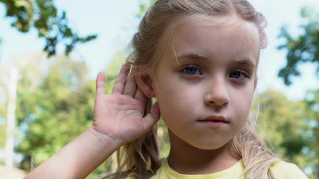 vídeos de stock, filmes e b-roll de menina caucasiana bonito que prende a mão perto da orelha que faz o gesto de escuta, notícia da bisbolhetice - surdo