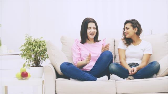 söt kaukasiska flicka berättar hennes afro-amerikanska vän en berättelse, ser allvarliga och oroande. - kvinna ventilationssystem bildbanksvideor och videomaterial från bakom kulisserna