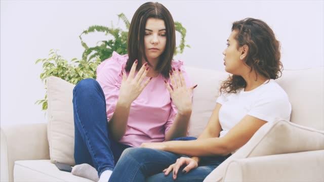söt kaukasiska flicka berättar hennes afro-amerikanska vän en berättelse, ser allvarliga, gest emotionaly. - kvinna ventilationssystem bildbanksvideor och videomaterial från bakom kulisserna