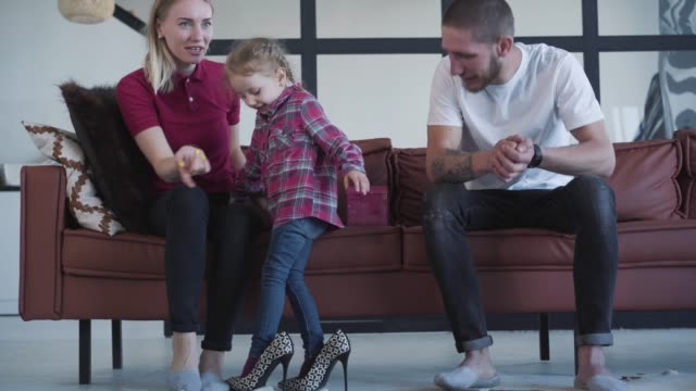 Cute cheerful little girl falling down wearing big mother's high-heels. Laughing parents raising up adorable daughter. Portrait of happy Caucasian family having fun together. Leisure, lifestyle, joy.