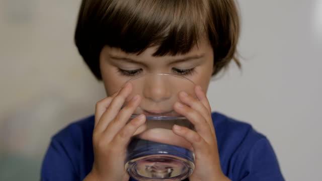 stockvideo's en b-roll-footage met schattig kind jongen het drinken van een glas water thuis. slow motion van kleine jongen drinkwater. close-up. kind drinkend een kop water met van citroen-gezonde lichaams zorg. - water drinken