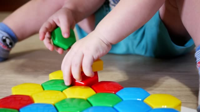 A cute child collects a picture from large multi-colored details. Playing with a puzzle A cute child collects a picture from large multi-colored details. Playing with a puzzle. child care stock videos & royalty-free footage