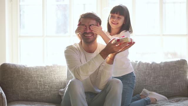 vídeos de stock, filmes e b-roll de filha bonito da criança que felici o paizinho no dia de pais que apresenta o presente - dia dos pais