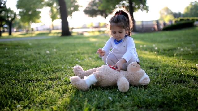 Cute child doctor saving her teddy bear friend