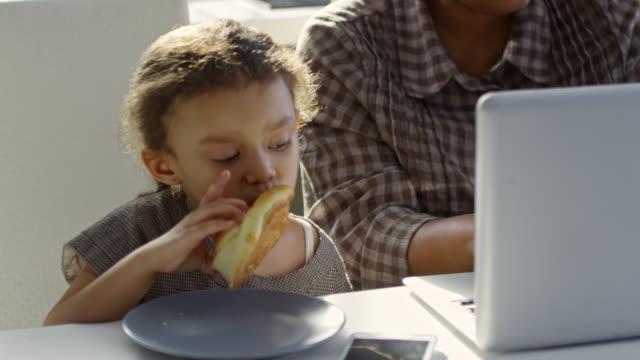 söta barn som äter bulle bredvid arbetande mamma - working from home bildbanksvideor och videomaterial från bakom kulisserna
