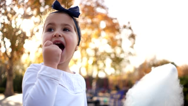 Cute child eating cotton candy at a city park Cute toddler girl enjoying a cotton candy snack outdoors in a city park. cotton candy stock videos & royalty-free footage