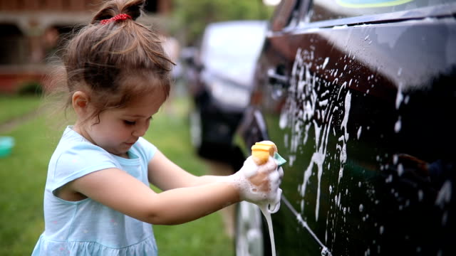Cute child helping a family wash their car Lovely and beautiful little toddler girl having fun by helping her family wash a car outdoors. chores stock videos & royalty-free footage