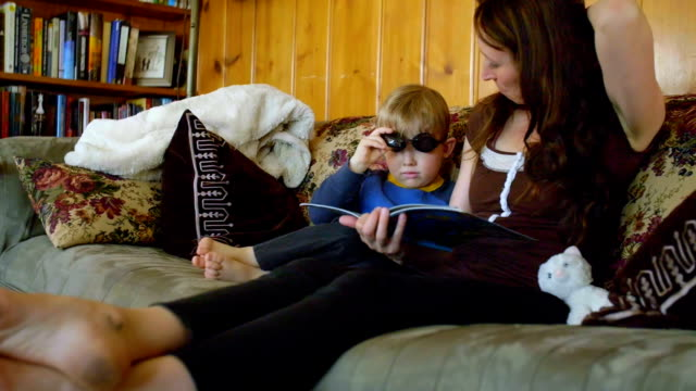 Cute child in goggles sits with mom reading a book video