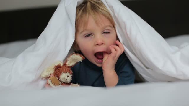 söt barn, liggande i sängen, leker med små saker leksak, leende glatt - duntäcke bildbanksvideor och videomaterial från bakom kulisserna