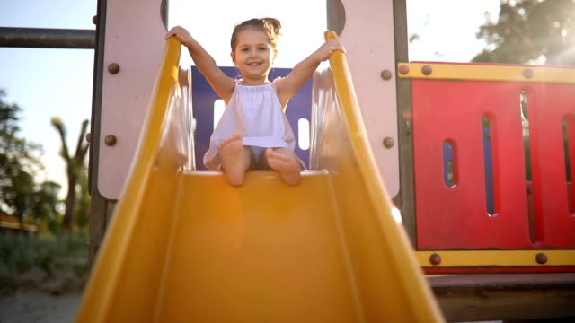 cute child on a slide - scivolo video stock e b–roll