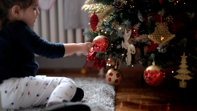 Cute child playing with Christmas ornaments