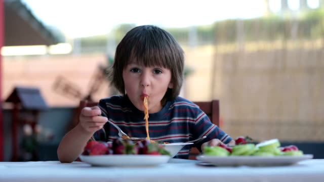 Cute child, preschool boy, eating spaghetti for lunch outdoors in garden, summertime Cute child, preschool boy, eating spaghetti for lunch outdoors in garden, summertime spaghetti stock videos & royalty-free footage