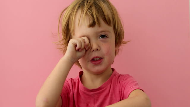 Cute child rubbing eye with plump hand Adorable little boy in pink t-shirt rubbing eye looking sleepy on pink background resting stock videos & royalty-free footage