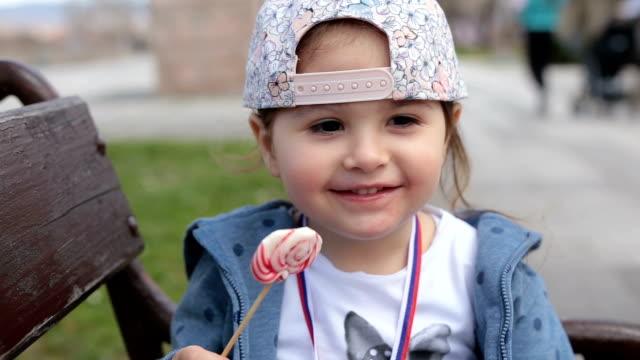 可愛的孩子坐在公園長椅上吃棒糖 - 波板糖 個影片檔及 b 捲影像
