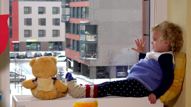 Cute child with best friend teddy bear sitting near window. Snow fall ビデオ