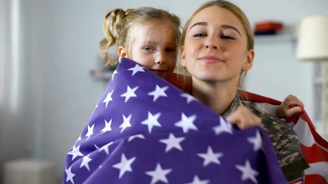 Cute child with US flag embracing military mother and smiling on camera, patriot Cute child with US flag embracing military mother and smiling on camera, patriot homecoming stock videos & royalty-free footage