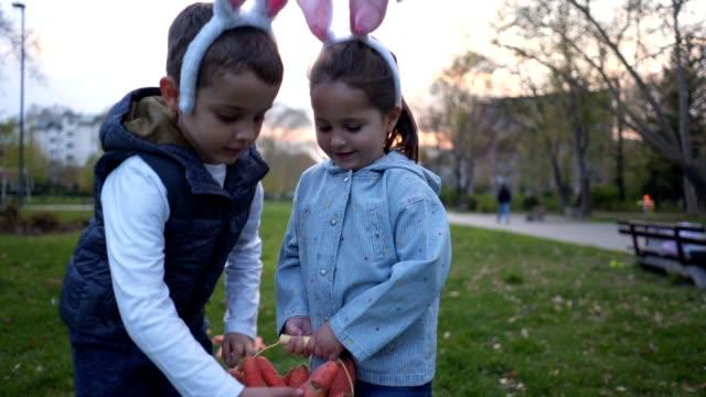 niedliche kinder, die während ostern karotten mit kaninchenohren sammeln - karotte peace stock-videos und b-roll-filmmaterial