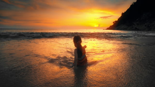 vídeos de stock e filmes b-roll de slo mo cute children girl playing on the beach at sunset - phuket