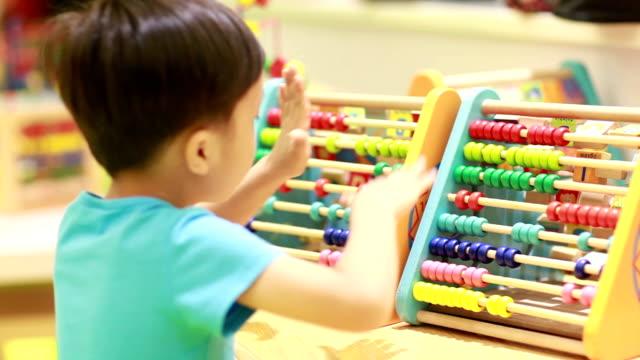 söta barn som leker på lekplatsen - abakus bildbanksvideor och videomaterial från bakom kulisserna
