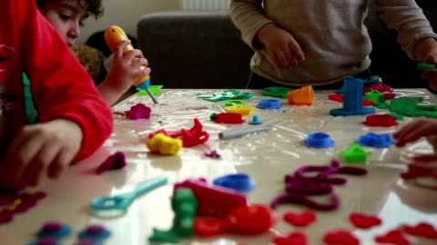 Cute children playing with dough in living room Close-up playing children. art and craft stock videos & royalty-free footage