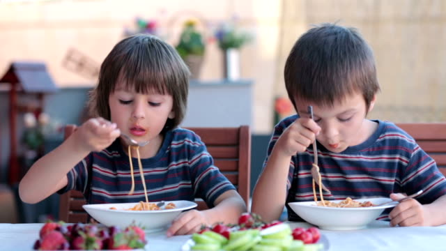 Cute children, preschool boys, eating spaghetti for lunch outdoors in garden, summertime Cute children, preschool boys, eating spaghetti for lunch outdoors in garden, summertime spaghetti stock videos & royalty-free footage