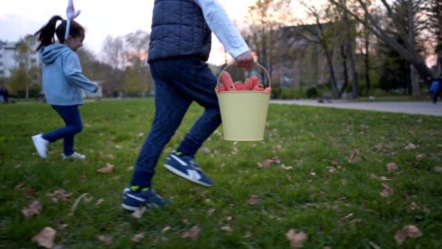 niedliche kinder laufen mit einem eimer, der mit karotten gefüllt ist zu ostern - karotte peace stock-videos und b-roll-filmmaterial